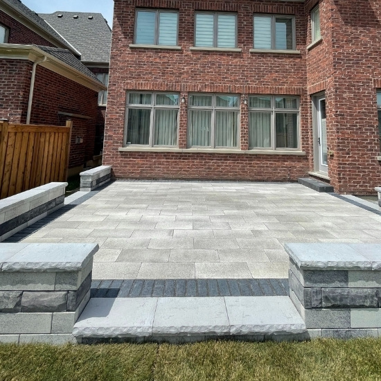 Image depicts a backyard with a new interlocking patio.