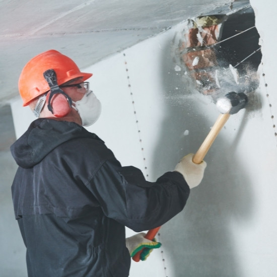 Demolition contractor breaking down drywall.