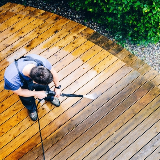 Power washing and sealing contractor washing a wood deck.